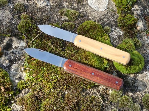 deux couteaux pliants pugnace, manche en buis échauffé et en bois exotique, lame pointe centrée nogentaise